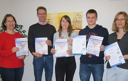 Das Foto zeigt Sara und Daniel mit ihren Fachlehrern Physik (links) und Chemie (rechts).